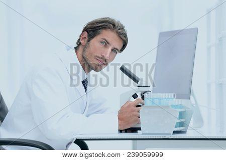 Male Chemist Scientific Reseacher using Microscope in Laboratory