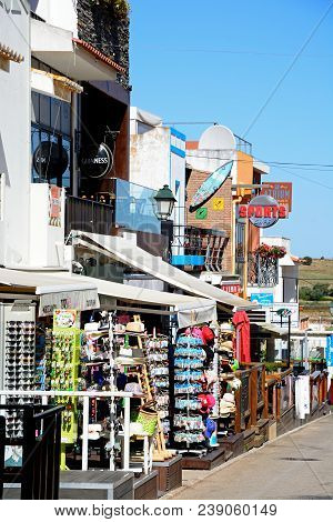 Alvor, Portugal - June 7, 2017 - View Along A Village Street With Shops And Restaurants Leading Towa