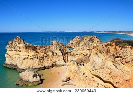 Portimao, Portugal - June 7, 2017 - Elevated View Of The Rocky Coastline With Tourists Relaxing On T