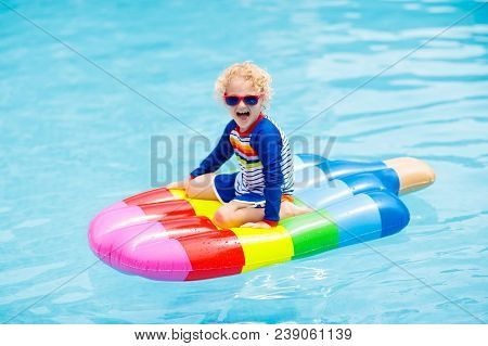Happy Child On Inflatable Ice Cream Float In Outdoor Swimming Pool Of Tropical Resort. Summer Vacati