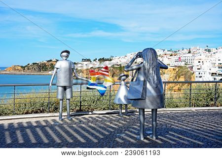 Albufeira, Portugal - June 10, 2017 - Metal Sculpture Of A Woman Taking A Photo Of Her Husband And D