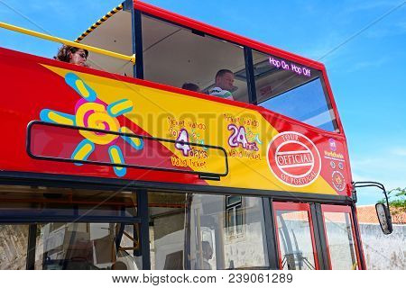 Albufeira, Portugal - June 10, 2017 - Tourists Aboard A Red And Yellow Open Topped Tour Bus, Albufei