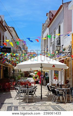 Silves, Portugal - June 10, 2017 - Restaurants Along An Old Town Street With Colourful Festival Bunt
