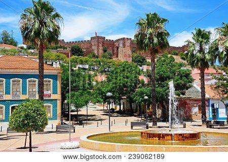 Silves, Portugal - June 10, 2017 - Fountain In The Praca Al Mutamid With The Castle To The Rear, Sil