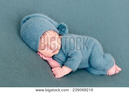 Infant baby boy sleeping in woolen costume with bare feet