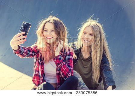 Happy girl friends taking a selfie on a summer day
