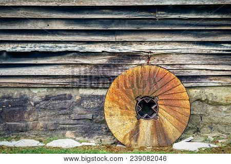 A Stone Wheel Sits Next To The Old Wooden Wall Of A Wisconsin Mill.