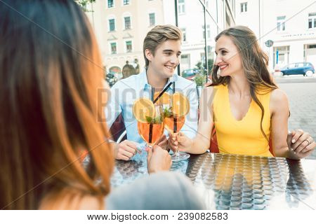 Young happy couple toasting with fresh orange cocktails with their mutual female friend at a trendy restaurant downtown poster