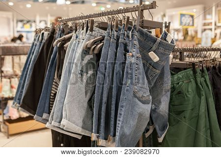 Jeans Shorts On The Store Shelf. Fashionable Clothes On The Shelves In The Store. Jeans Hanging On T