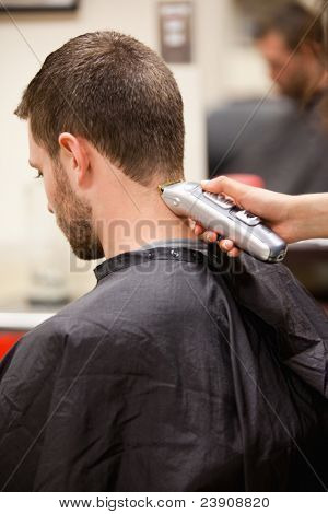 Portrait of man having a haircut with a hair clippers