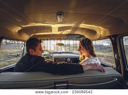 Young Wedding Couple Sitting Smiling Inside Retro Car And Looking At Each Other. Just Married Embrac
