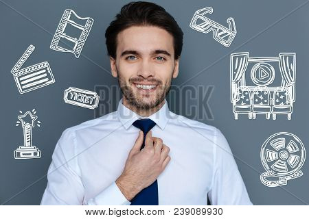 Famous Actor. Cheerful Successful Famous Actor Smiling And Touching His Tie While Getting Ready For