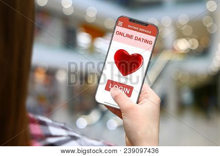 Online Dating Idea, Girl With Frameless Phone On Blurred Mall Background