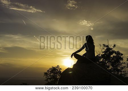 Girl Practicing Yoga On The Mountain Cliff In Sunset. Young Girl Meditating In Yoga Position In Suns