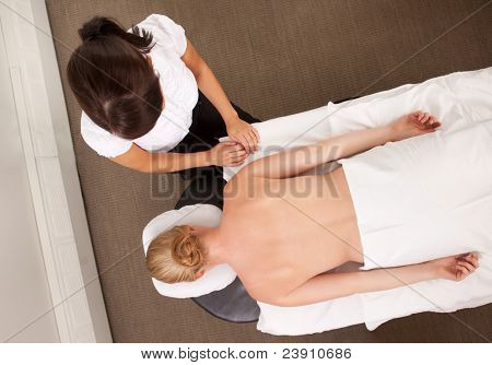 Female acupuncturist in clinic with a patient ready for therapy