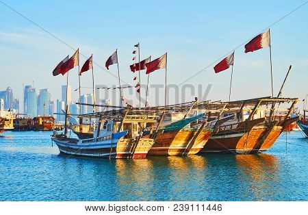 Traditional Dhow Boats With Flags Of Qatar Are Docked In Harbor Of Doha, Such Vessels Are Popular Fo