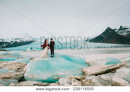 Iceland Wedding. Beautiful Newlyweds Stand On Glacier Near Jokulsarlon In Cold Windy Day. Copy Space