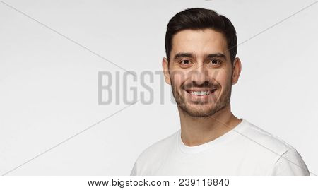 Closeup Headshot Of Young European Caucasian Man Isolated On Gray Background Wearing Casual White T-