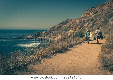 Young Couple Walking On A Rugged Trail With Their Surfboards In Palos Verdes Estates, California