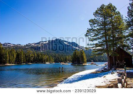 Shallow Shoreline On Mountain Lake With Snow Melting In Springtime