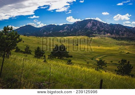 Beautiful Flatirons Mountain And Valley With Winding Road On A Summer Day With Blue Sky And Clouds,