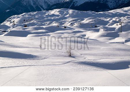 Snow Landscape With Chair Lift In The Background And Snow Dunes And Empty Space On The Bottom