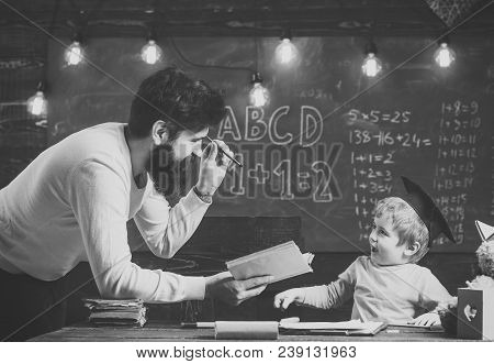 Wunderkind And Genius Concept. Father, Teacher Reading Book, Teaching Kid, Son, Chalkboard On Backgr