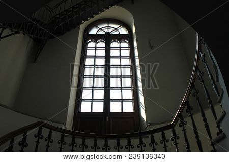 Antique Glass Window And Spiral Staircase In Old Historical Building. Architecture Detail Of Retro O