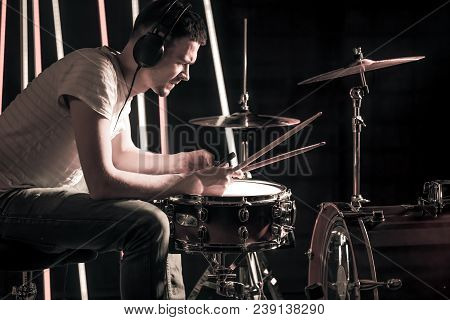 Man Plays The Drums In The Headphones. On The Background Of Colored Lights.