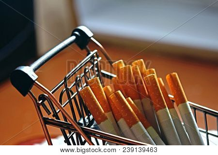 A Bunch Of Cigarettes Lying In A Metal Mini Cart. Bad Habit. The Dependence On Nicotine.