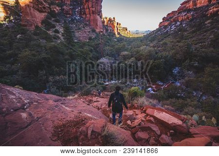 Male Hiker Descending A Steep And Rugged Red Rock Tail From A Scenic Overlook Of Fay Canyon, Coconin