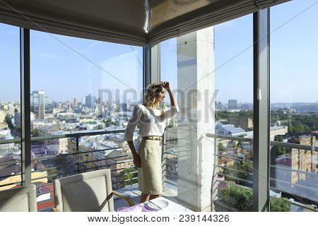 Nice Woman Standing At Restaurant Near Window With Buildings In Background. Concept Of Catering Esta