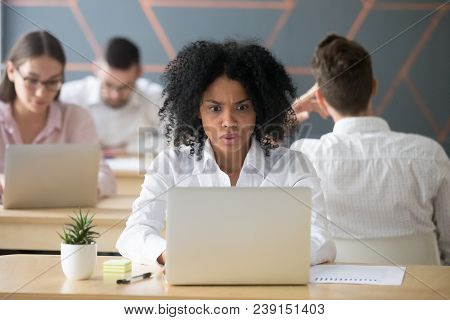 Shocked African Woman Looking At Laptop In Shared Office, Stressed Black Female Employee Terrified R