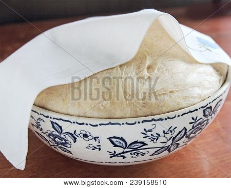 Bread Dough Rises In A Bowl Partially Covered With A Dish Towel