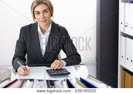 Portrait of female bookkeeper or financial inspector  making report, calculating or checking balance. Copy space area. poster