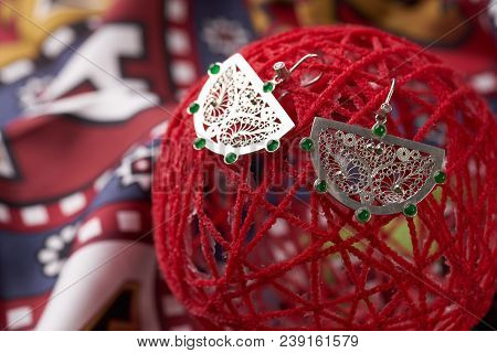 Pair Of Silver Earrings With Emerald Gemstones On A Red Decorative Ball Background , Close-up. Luxur