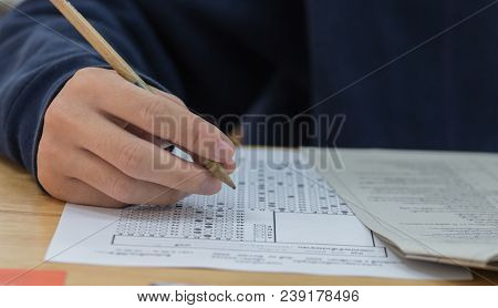 High School Or University Student Hands Taking Exams, Writing Examination On Paper Answer Sheet Opti