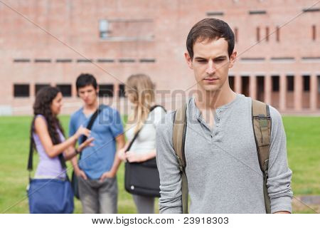 Lonely student posing while his classmates are talking outside a building