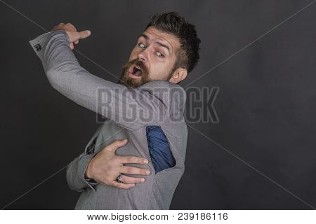Bearded Man Look At Torn Coat With Surprise. Bearded Man With Beard With Ripped Hole On Seam.