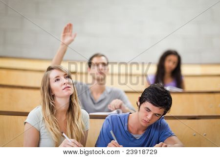 Students taking notes while their classmate is raising his hand in an amphitheater
