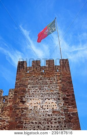 Silves, Portugal - June 10, 2017 - View Of The Medieval Castle Tower With A Portuguese Flag Atop, Si