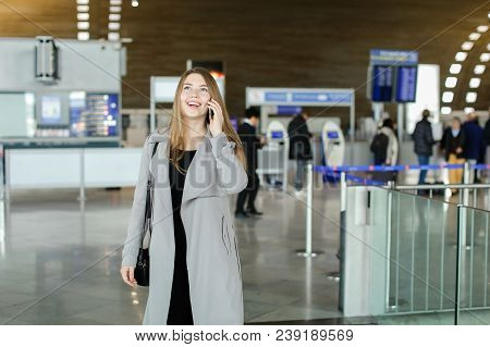 Young Businesswoman Talking By Smartphone At Airport Hall, Wearing Grey Coat And Bag. Concept Of Con