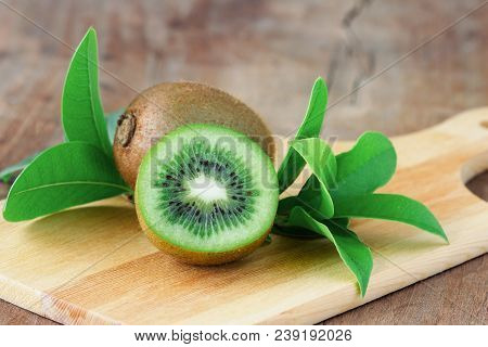 Fresh And Juicy Kiwi Fruit And A Half On Cutting Board. Ripe Kiwi Fruits On Wood Table In Side View