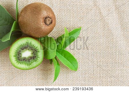 Fresh And Juicy Kiwi Fruit And A Half On Sack In Top View Flat Lay With Copy Space. Ripe Kiwi Fruits
