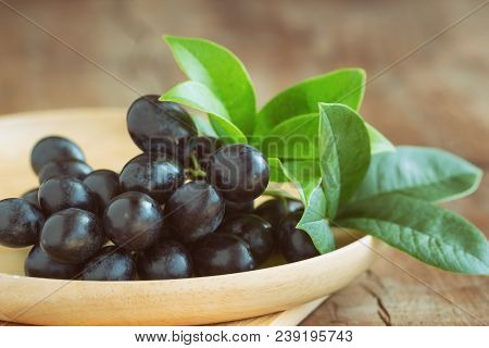 Fresh Seedless Red Grape On Wooden Plate. Black Grapes Put On Wood Table In Side View With Copy Spac