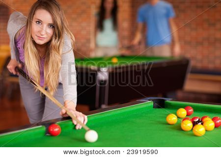 Cute woman playing snooker in a home student