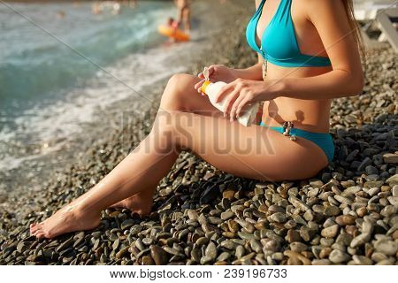 Slim Woman Tanned Lower Body In Shape Lying On Pebble Beach Near Sea Waves And Surf With Sunblock Cr