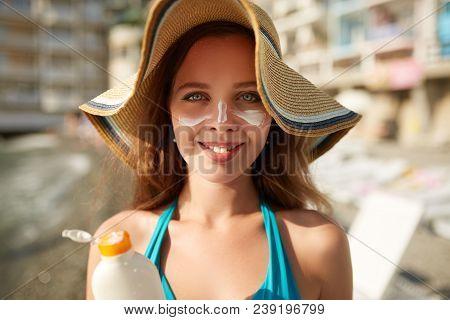 Suntan Lotion. Woman Applying Sunscreen Solar Cream On Face. Beautiful Happy Cute Girl Puts Suntan C