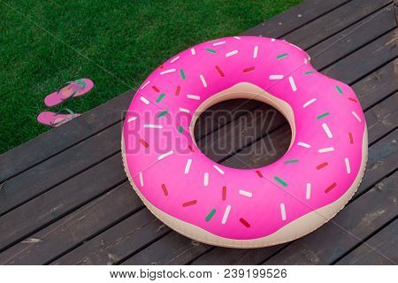 The Inflatable Circle In The Form Of A Donut Lies On A Wooden Pier. Next To It Lie The Shale On The