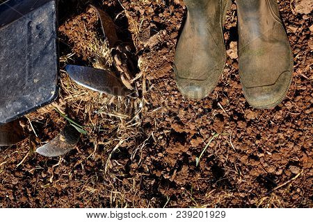 Worker Boots And Motor Cultivator On Soil.